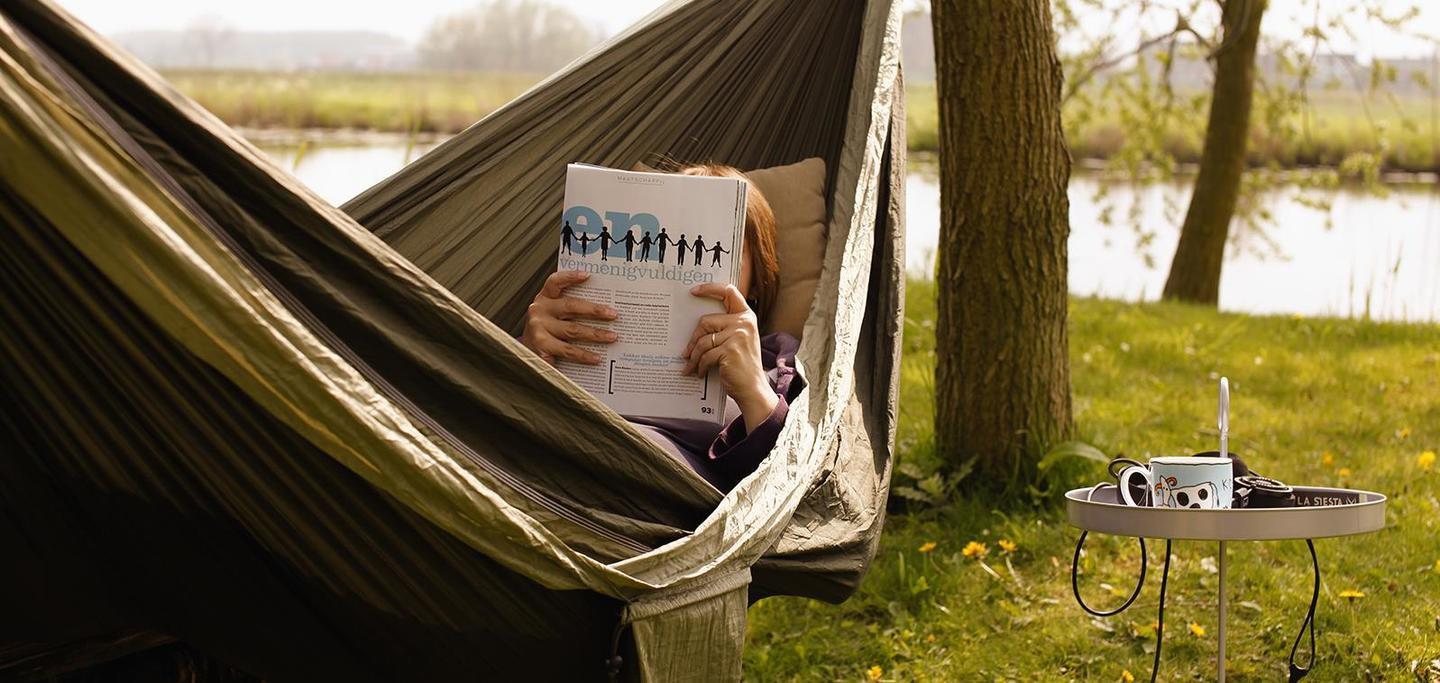 Person reading magazine in hammock