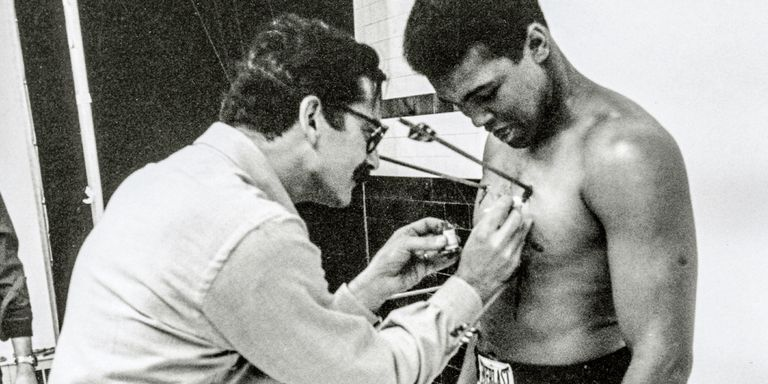 George Lois pasting arrows on Muhammed Ali's body