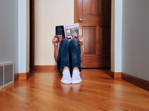 Young person reading magazine while sitting on the floor