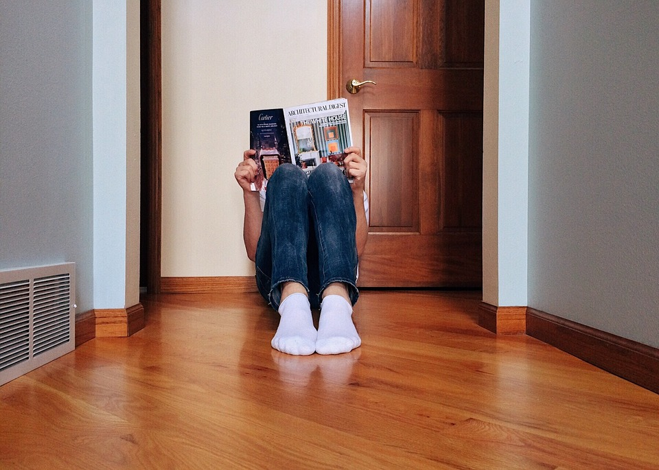 young person reading magazine sitting on floor