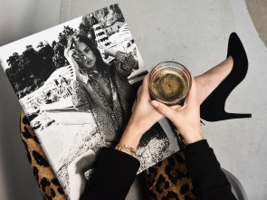 woman's hands holding coffee cup and magazine