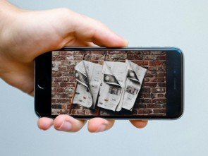 hand showing mobile phone with newspapers depicted on screen