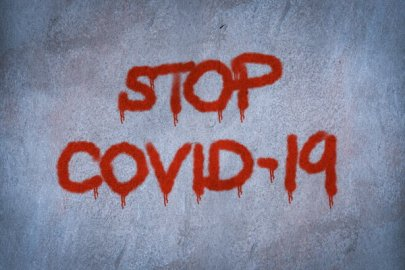 writing on concrete wall: Stop Covid-19