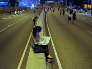 Woman reading the paper while sitting in the middle of the street